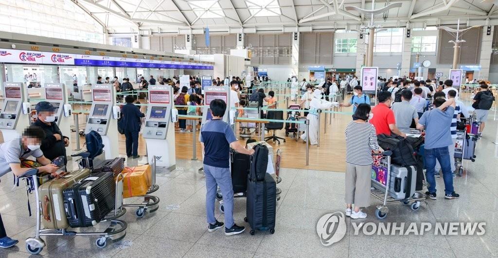 资料图片:9月4日下午,在仁川国际机场,即将飞往中国北京的现代汽车员工正在办理登机手续。经中国政府批准,现代汽车集团于3-4日投入3架包机送600余名员工及其家属前往北京。 韩联社