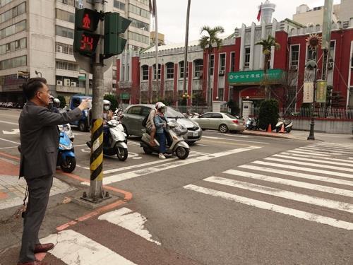 资料图片:2019年3月13日,金尚浩站在赵明河义举街头,手指赵明河义举前所在地。 金尚浩供图(图片严禁转载复制)