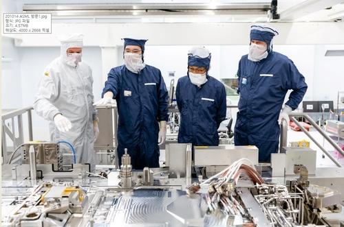 当地时间10月13日,在位于荷兰埃因霍温的阿斯麦尔公司总部,三星电子副会长李在镕(左二)了解EUV光刻设备运转情况。 韩联社/三星电子供图(图片严禁转载复制)