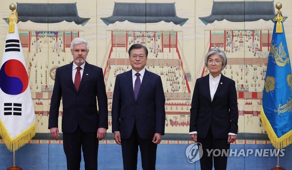10月16日,在青瓦台,韩国总统文在寅(中)和新任德国驻韩大使迈克尔·赖芬施图尔合影。 韩联社