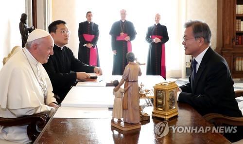 资料图片:2018年10月,总统文在寅(右)访问教廷与教皇方济各交谈。 韩联社