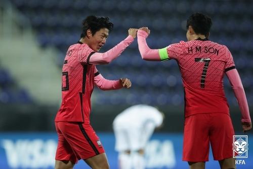 黄义助(左)和孙兴慜庆祝进球。 韩联社/大韩足球协会供图(图片严禁转载复制)