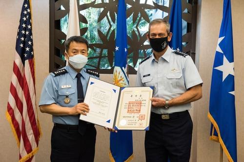 当地时间11月19日,在美太平洋空军司令部,李成龙(左)向肯尼斯·威尔斯巴授予了报国勋章国仙章。 韩联社/韩国空军供图(图片严禁转载复制)