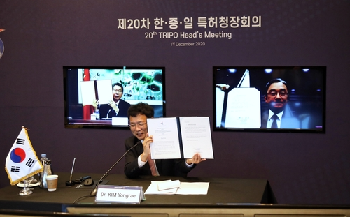 12月1日,韩国专利厅厅长金龙来(中)出席在线上举行的第20次韩中日知识产权局局长政策对话会,手举协议文本。 韩联社/韩国专利厅供图(图片严禁转载复制)