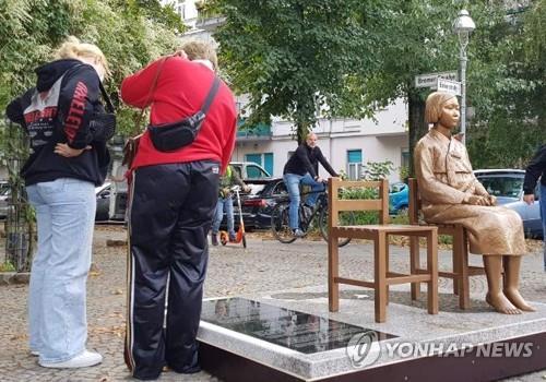 """资料图片:当地时间11月25日,在德国柏林,当地居民阅读""""和平少女像""""的碑文。 韩联社"""