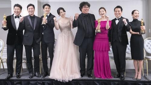 资料图片:2月10日,《寄生虫》导演奉俊昊(中)和演员们获得奥斯卡金奖后合影留念。 韩联社