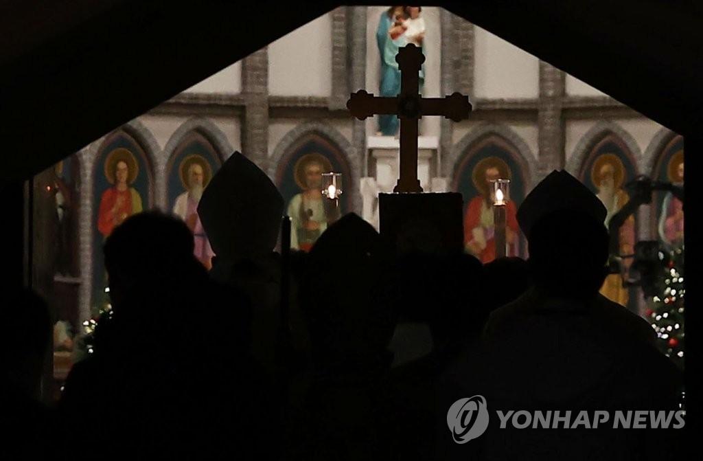 12月24日下午,在位于首尔市中区的明洞大教堂首次举行非接触式圣诞弥撒,廉洙政和司祭团步入教堂。 韩联社