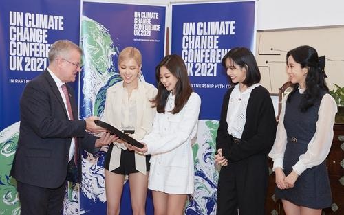 2月25日,在英国驻韩大使馆,英国驻韩大使西蒙·史密斯(左一)向BLACKPINK颁发第26届联合国气候变化大会(COP26)宣传大使任命证书。 韩联社/YG娱乐供图(图片严禁转载复制)
