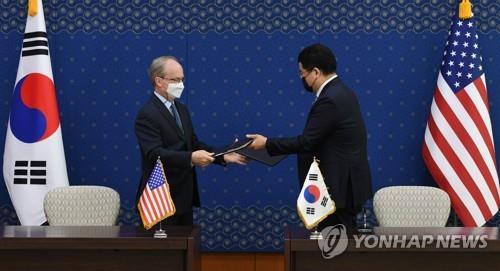 4月8日,在首尔外交部大楼,韩国外交部第一次官崔钟建(右)和美国驻韩大使馆临时代办拉普森签字后互换第11份防卫费分担特别协定。 韩联社