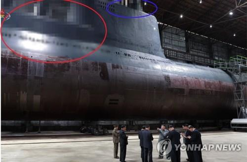 资料图片:2019年7月23日,朝鲜中央电视台播出了朝鲜国务委员会委员长金正恩视察潜艇建造现场的画面。图中疑似为潜射弹道导弹发射管(红圈)和疑似为雷达及潜望镜(篮圈)的部分被马赛克处理。 韩联社朝鲜央视画面(图片仅限韩国国内使用,严禁转载复制)