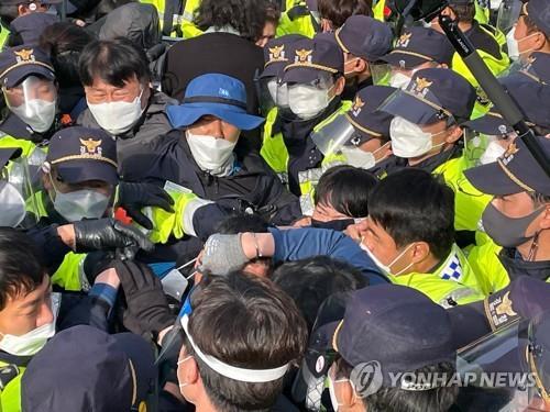 """资料图片:4月28日上午,在位于庆尚北道星州郡的""""萨德""""反导基地入口,警方驱离示威人员。 韩联社"""