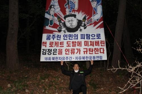 """资料图片:韩国脱北者团体""""自由北韩运动联合""""代表朴相学高举反朝标语。 """"自由北韩运动联合""""供图(图片严禁转载复制)"""