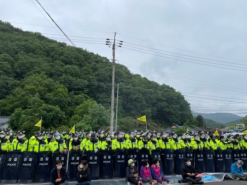 5月18日上午,在庆尚北道星州郡的萨德基地入口,警方筑成人墙阻挡居民堵路拦车。 韩联社