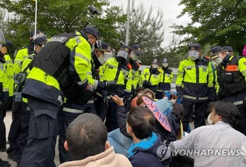"""5月25日,在庆尚北道星州郡草天面韶成里的""""萨德""""基地入口,警方驱散示威人员。 韩联社"""