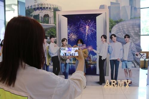 中国粉丝在以防弹少年团为背景的宣传墙前拍照留念。 韩联社