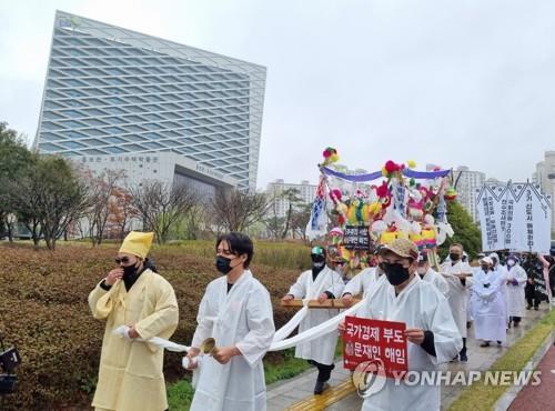 资料图片:3月20日,在庆尚南道晋州市的韩国土地住宅公社总部,一公民团体会员进行表演,谴责该公社职员非法炒地事件。 韩联社
