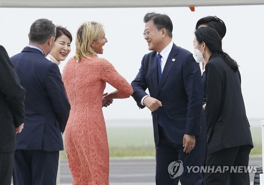 当地时间6月11日下午,韩国总统文在寅(右)抵达英国康沃尔纽基机场,与到机场迎接的人士致意。文在寅此行将出席七国集团峰会。 韩联社