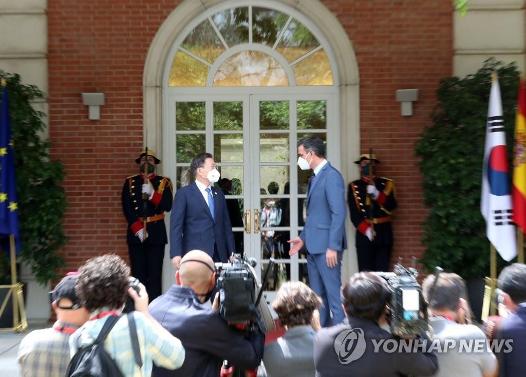 当地时间6月16日,在马德里,韩国总统文在寅(左)与西班牙首相佩德罗·桑切斯举行会谈并合影。 韩联社