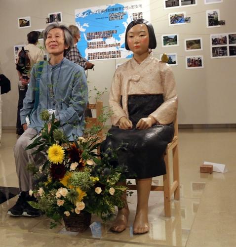 """7月6日,在日本爱知县名古屋市民展馆""""荣"""",一名参观者坐在和平少女像旁边拍照。 韩联社"""