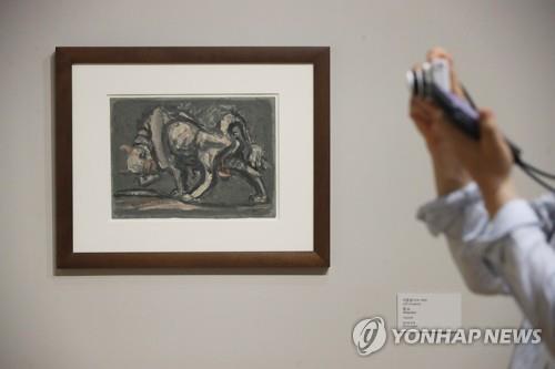 """7月20日,在首尔市钟路区的国立现代美术馆首尔馆,""""李健熙藏品特展——韩国美术名作""""媒体见面会举行。图为参会者观赏李仲燮的作品《黄牛》。 韩联社"""