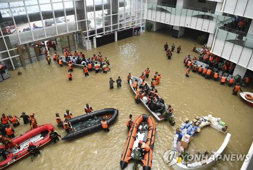 资料图片:7月22日,中国河南省郑州一家医院被洪水困围,搜救队正在转移患者。 韩联社/新华社