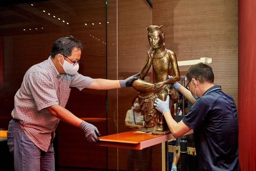 国立中央博物馆工作人员正在搬运第83号国宝半跏思惟像。 韩联社/国立中央博物馆供图(图片严禁转载复制)