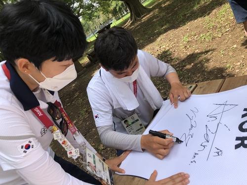 韩国射箭选手安山(左)和金济德在运动服上签名。 韩联社/大韩射箭协会供图(图片严禁转载复制)