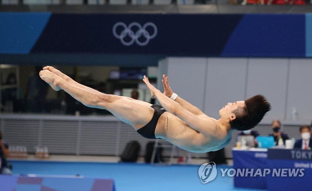 8月3日,在东京水上运动中心进行的东京奥运会男子3米跳板跳水决赛中,韩国选手禹河蓝正在翻跳入水。 韩联社