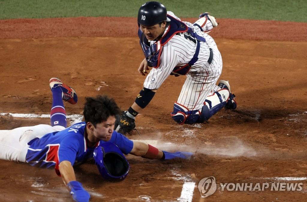 8月4日,在日本横滨棒球场,韩国队和日本队进行东京奥运会棒球半决赛。图为韩国球员朴海旻借队友姜白虎打出安打的机会跑回本垒得分。 韩联社