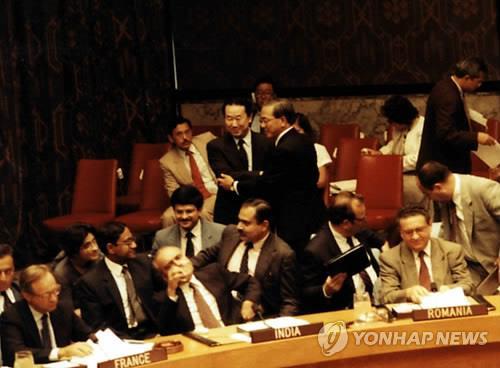 资料图片:1991年9月17日,在联合国总部,韩朝加入联合国成定局后,韩国大使卢昌熹(右)和朝鲜驻联合国大使朴吉渊在安理会会场握手相互祝贺。 韩联社