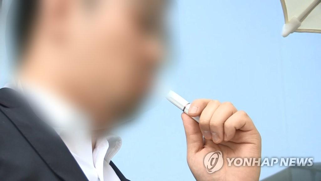 资料图片:一名烟民在吸电子烟。 韩联社