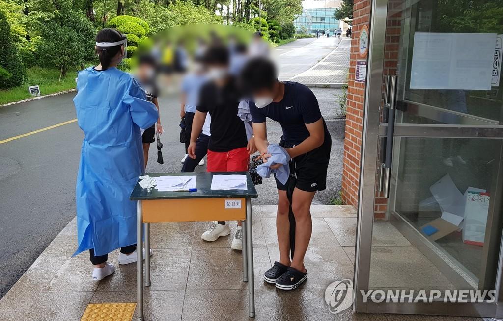 资料图片:釜山市一高中学生接受新冠病毒检测。 韩联社/海云台区卫生站供图(图片严禁转载复制)
