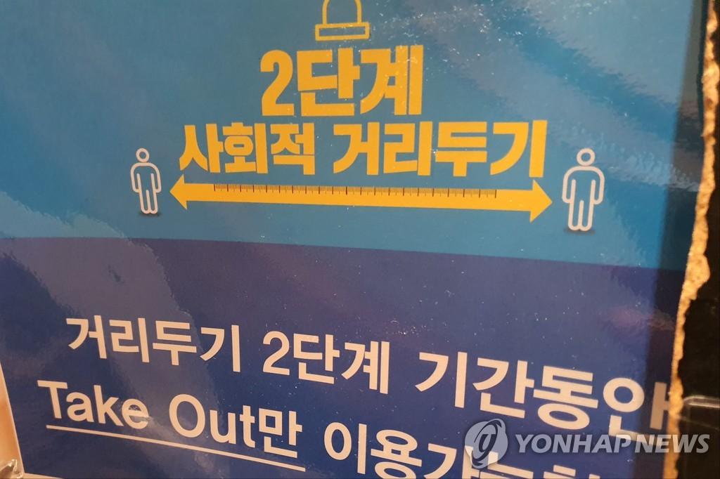 """资料图片:一餐厅的""""保持社交距离""""告示牌 韩联社"""