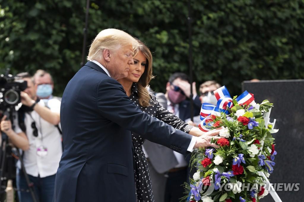当地时间6月25日,在位于美国华盛顿的韩国战争纪念公园,特朗普夫妇向韩战纪念碑献花。 韩联社/欧新社(图片严禁转载复制)