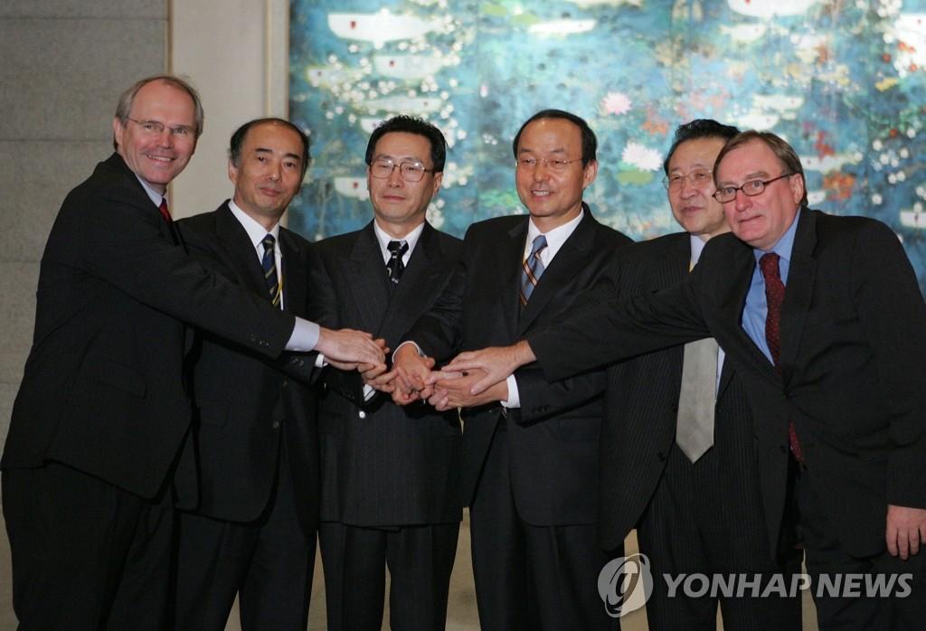 资料图片:2005年9月19日,在北京钓鱼台国宾馆,朝核问题六方会谈通过《9·19共同声明》后,六方代表握手合影。(韩联社)