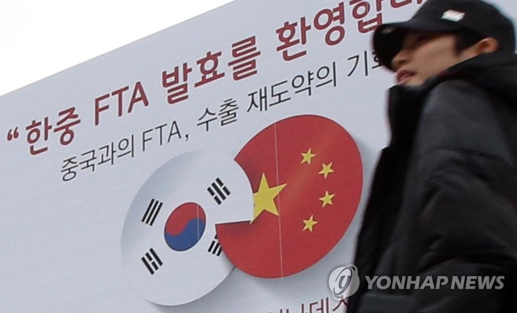 """资料图片:这是在首尔COEX会展中心外墙上悬挂的横幅,写有""""欢迎韩中自贸协定(FTA)生效""""的韩文字句,图片摄于2015年12月20日。韩中于2015年6月1日签署自贸协定,协定于12月20日正式生效。(韩联社)"""