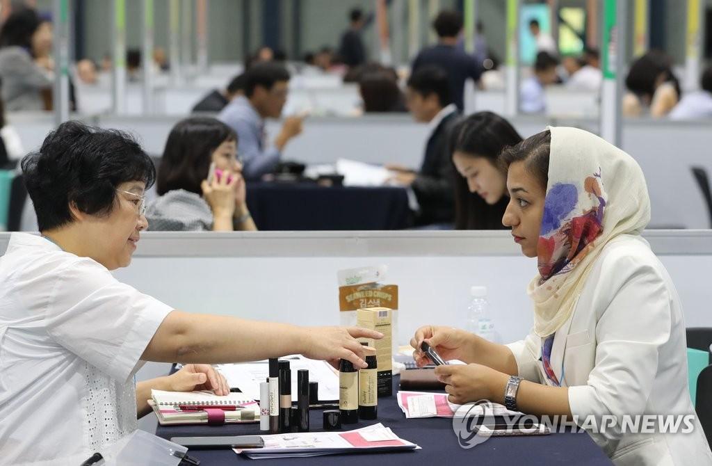 资料图片:一名中东采购商与韩国化妆品厂商讨论清真认证化妆品。(韩联社)
