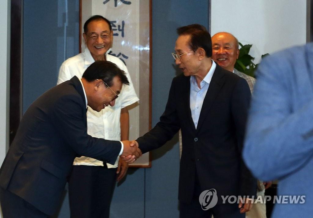 执政党新党首和前总统李明博交谈