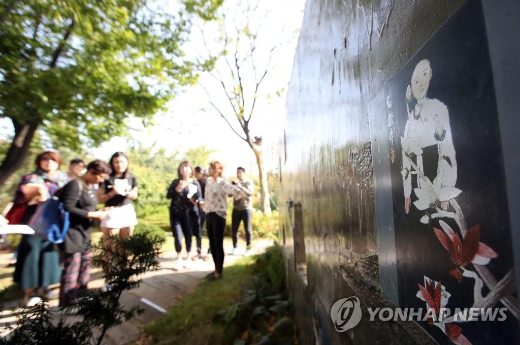 日本游客欣赏慰安妇受害者壁画作品