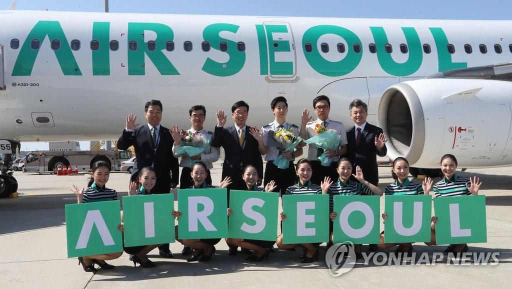 资料图片:2016年10月,首尔航空1号飞机抵达仁川机场。图为首尔航空乘务人员庆祝飞机抵达仁川。(韩联社)