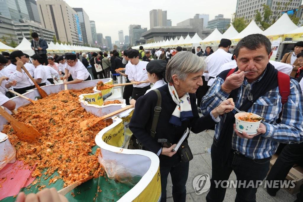 """资料图片:2016年10月26日,在首尔光化门广场,参加""""第四届韩餐日""""活动的外国游客品尝拌饭。(韩联社)"""