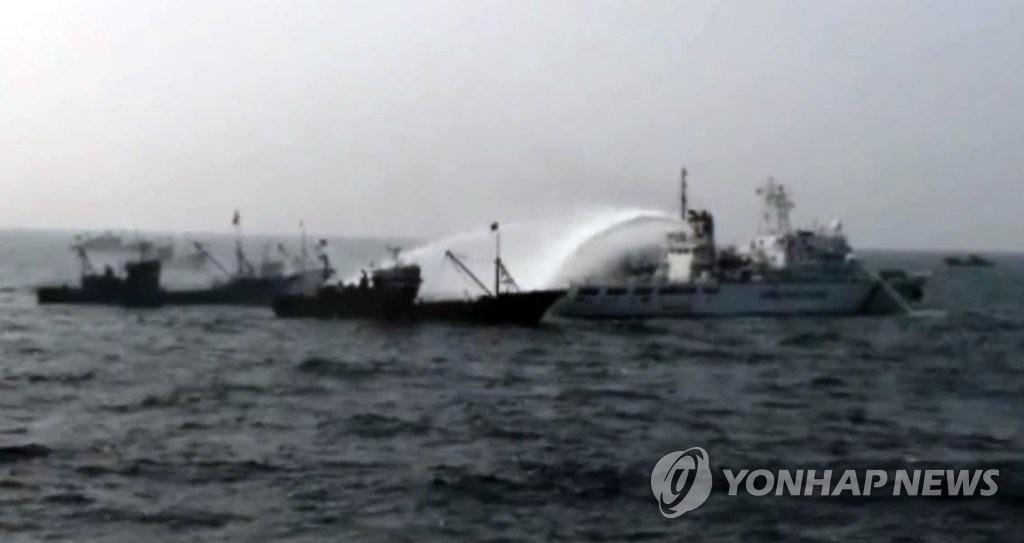 韩海警用消防炮压制阻挠扣船的中国渔船