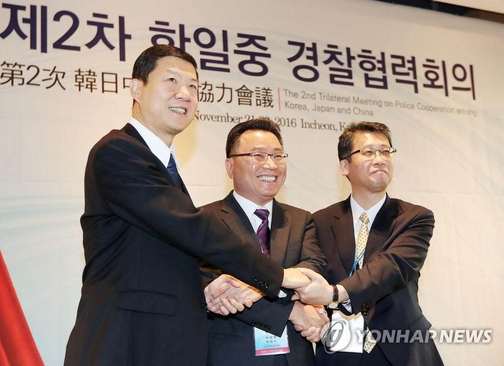 韩中日警方代表握手合影