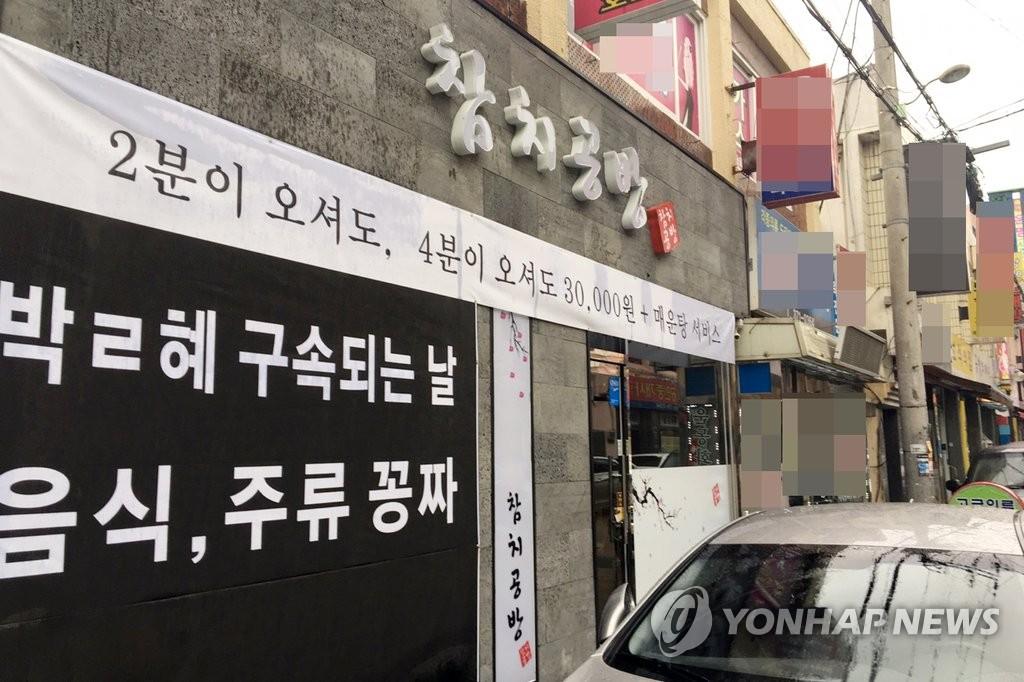 商家挂横幅:朴槿惠被捕餐饮免费
