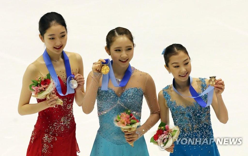 2月25日,获得第8届亚冬会花样滑冰女子单人滑项目金牌的韩国选手崔多彬(中)与银牌、铜牌获得者一起站在领奖台上。(韩联社)