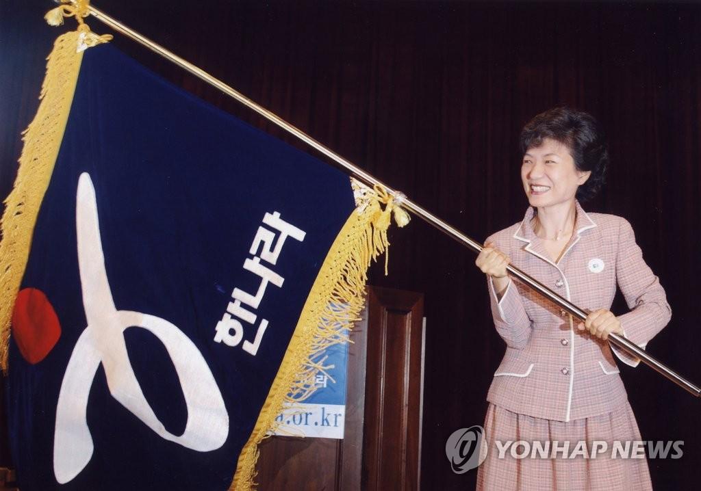资料图片:2004年,朴槿惠在第17届国会议员当选人大会上挥舞大国家党的党旗。(韩联社)