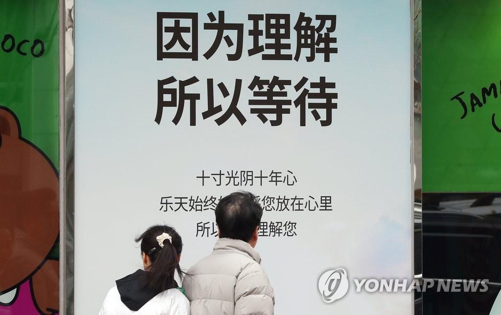 """资料图片:2017年3月,乐天百货明洞本店外张贴写有""""因为理解,所以等待""""的海报。(韩联社)"""