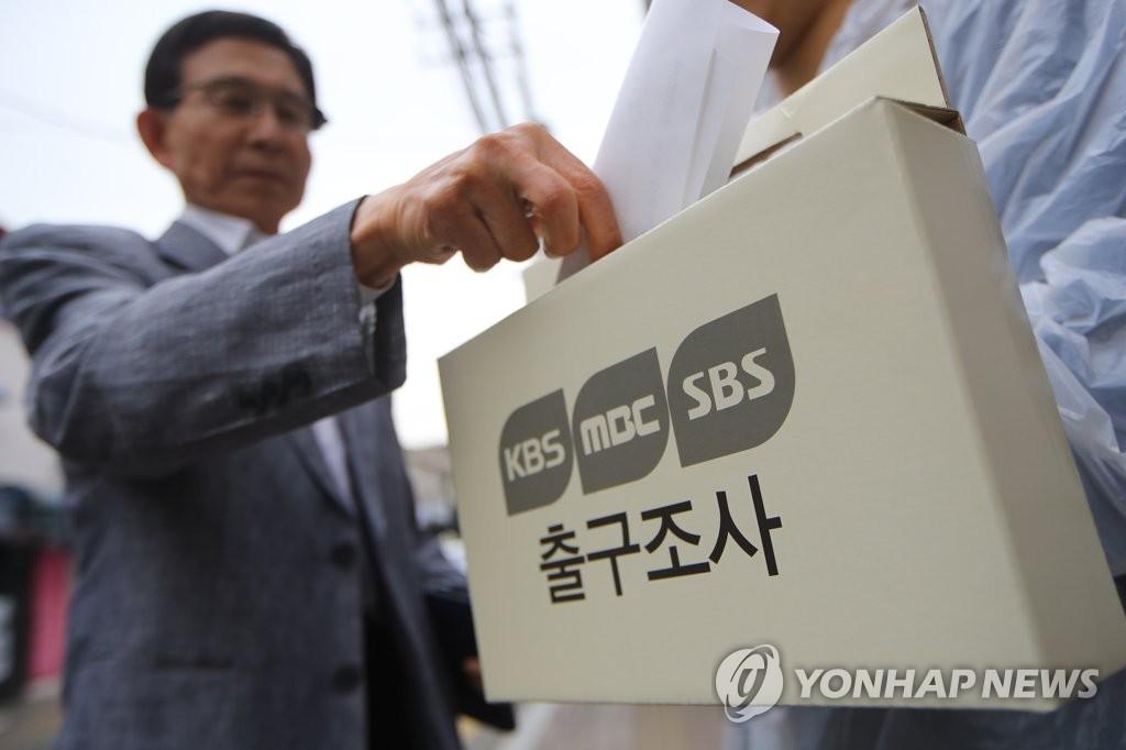 资料图片:5月9日,在首尔龙山区梨泰院2洞第2投票站前,韩国三大电视台出口民调工作人员针对选民进行调查。(韩联社)