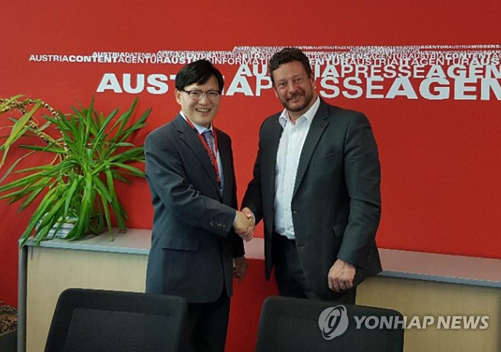 当地时间5月16日,在位于维也纳的奥地利通讯社(APA)总部,韩联社常务理事赵福来(左)与APA相关人士握手合影留念。(韩联社)