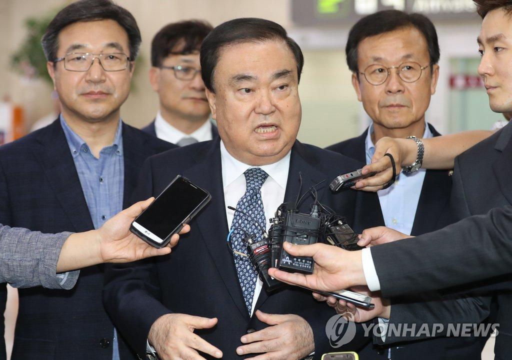 5月20日,在金浦机场,韩总统特使文喜相(中)答记者问。(韩联社)